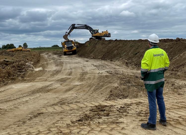 A man watching an excavator at work.